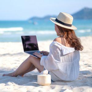 Frau mit Computer am Strand